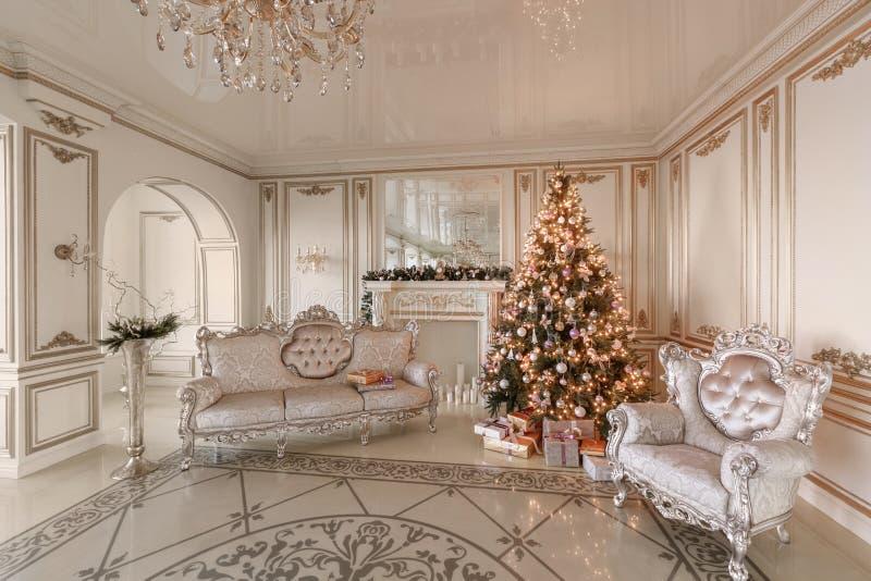 Manhã de Natal apartamentos luxuosos clássicos com uma chaminé branca, árvore de Natal decorada, sofá, grandes janelas fotos de stock