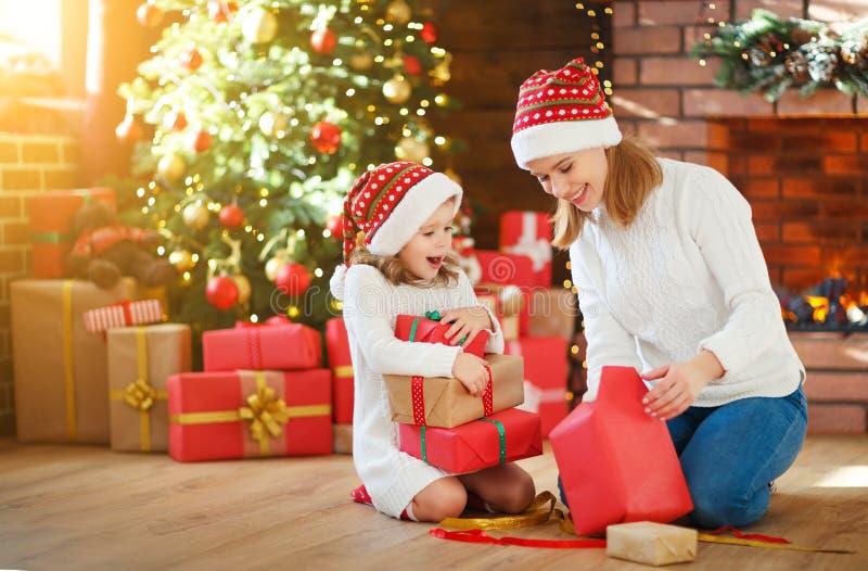 Manhã de Natal a mãe e a filha da família desembalam, presente aberto fotos de stock royalty free