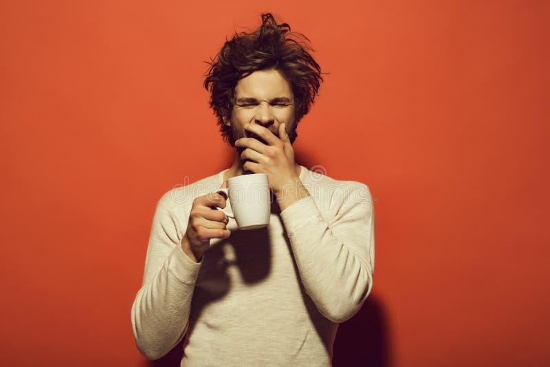 Manhã de um homem homem de bocejo sonolento com o copo do chá ou do café fotografia de stock royalty free
