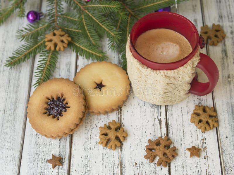 Manhã do inverno, xícara de café com os suportes de copo feitos malha, cookies do pão-de-espécie com os ramos de árvore do abeto  fotos de stock
