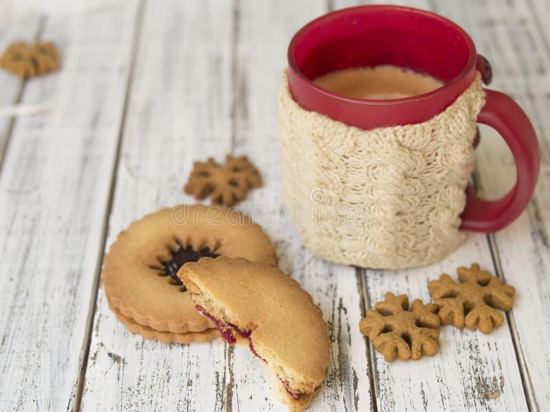 Manhã do inverno, xícara de café com os suportes de copo feitos malha, pão-de-espécie e cookies da baunilha em um fundo de madeir imagem de stock royalty free