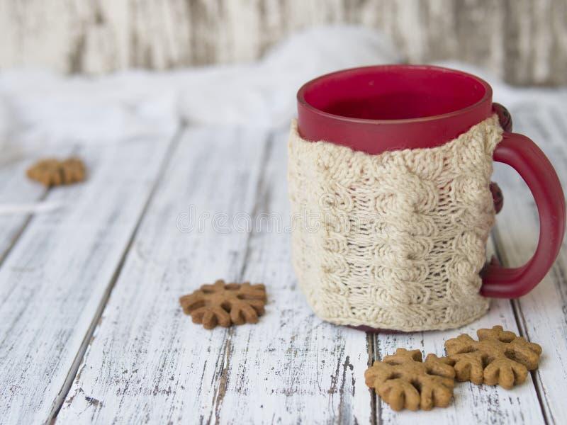 Manhã do inverno, xícara de café com os suportes de copo feitos malha, pão-de-espécie e cookies da baunilha em um fundo de madeir foto de stock royalty free