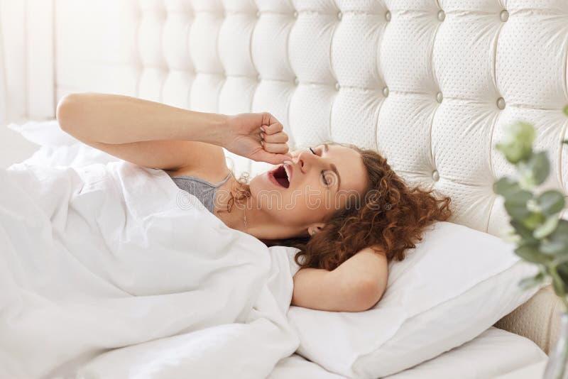 Manhã e conceito do despertar Bocejos da jovem mulher como encontra-se no comf imagem de stock royalty free