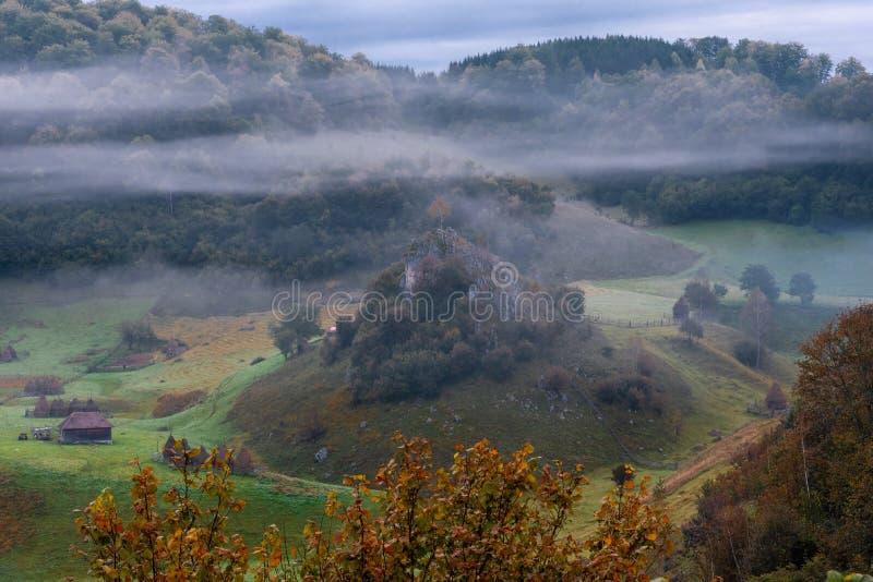 Manh? enevoada fria no lugar remoto impressionante, vila de Fundatura Ponorului, Rom?nia imagens de stock royalty free