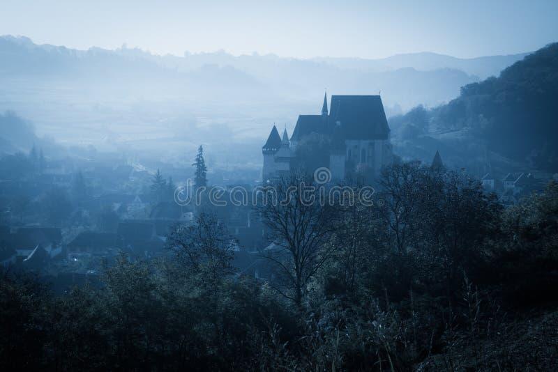 Manhã enevoada misteriosa sobre a vila de Biertan, a Transilvânia, Romênia foto de stock royalty free