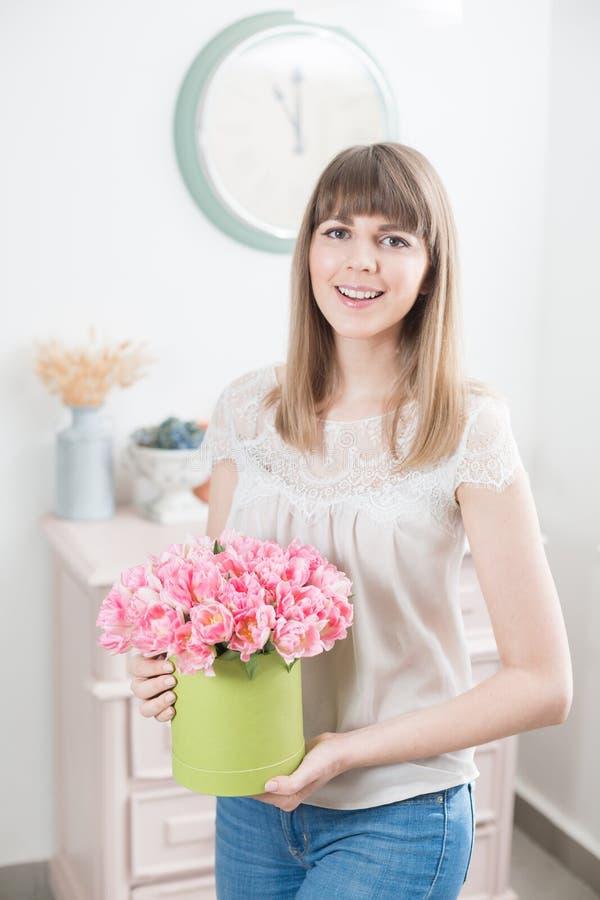 Manhã ensolarada da mola Mulher feliz nova que guarda um grupo bonito de tulipas cor-de-rosa em suas mãos Presente para uma menin foto de stock royalty free