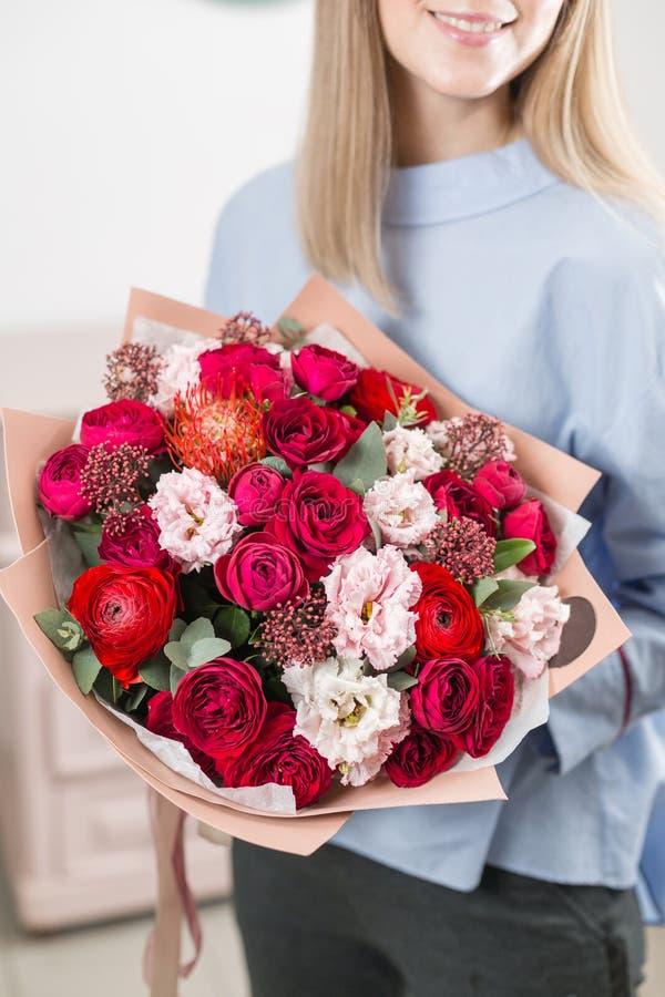 Manhã ensolarada da mola Mulher feliz nova que guarda um ramalhete luxuoso bonito de flores misturadas o trabalho do florista em imagem de stock