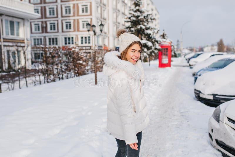 Manhã ensolarada do inverno de surpreender a menina bonita que anda na rua completa com neve Tempo frio, humor do Natal, brightfu foto de stock