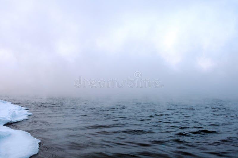 Manhã gelado adiantada do inverno no riverbank As águas escuras do rio flutuam lentamente As banquisas de gelo no ` s da água afi imagem de stock
