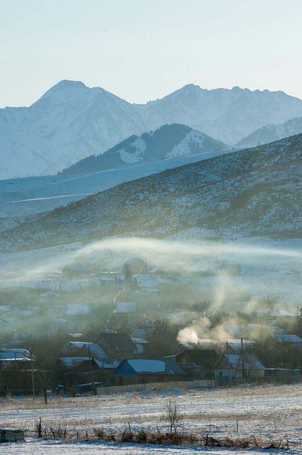 Manhã gelado da montanha, o fumo do fogão espalha no imagem de stock