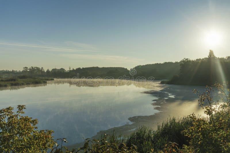 Manhã, nascer do sol sobre um rio coberto com a névoa da manhã no outono imagem de stock