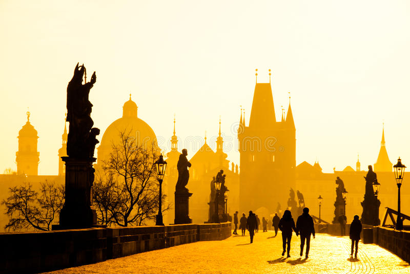 Manhã nevoenta em Charles Bridge, Praga, República Checa Nascer do sol com as silhuetas de povos, de estátuas e de velho de passe fotografia de stock