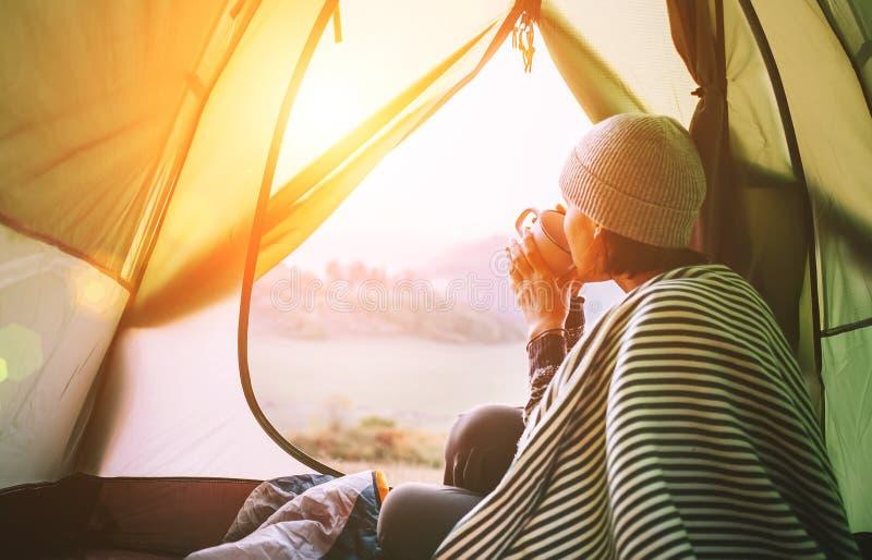 Manhã no acampamento do temt A mulher com o copo do ch? quente senta-se na barraca de acampamento foto de stock royalty free
