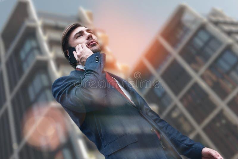 Manhã ocupada Homem de negócios à moda atrativo no terno que fala no telefone ao andar através das ruas da cidade com imagens de stock