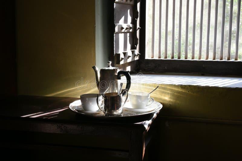 Manhã romântica, luz do nascer do sol que brilha no grupo de chá de prata dos utensílios fotografia de stock royalty free