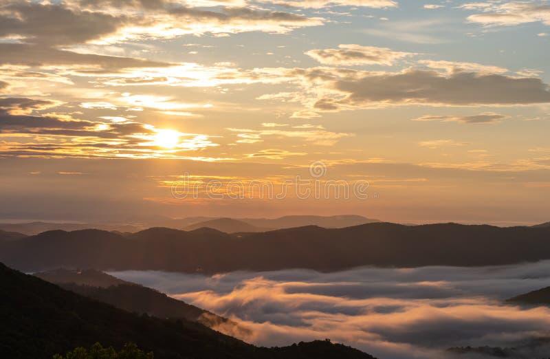 A manhã Sun consome baixas nuvens de encontro da manhã imagens de stock royalty free