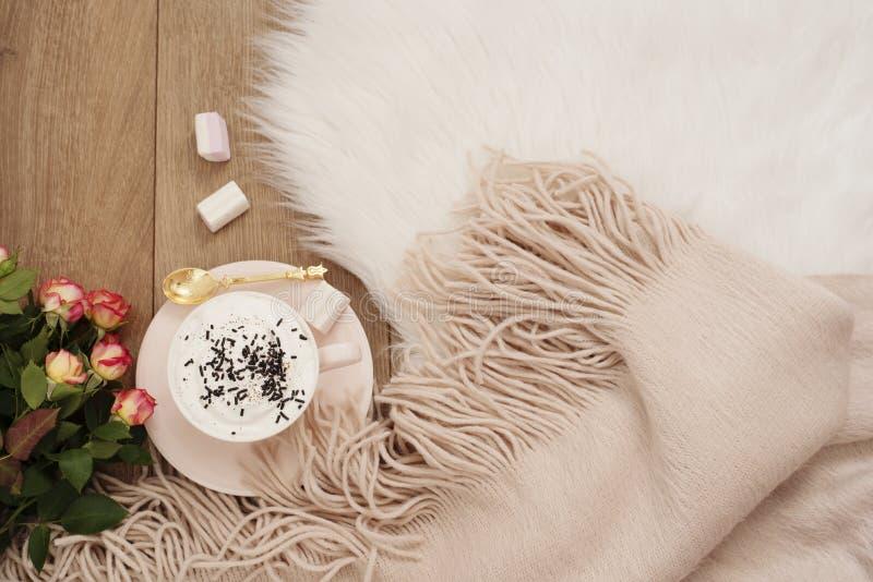 Manhãs acolhedores do inverno Cappuccino, ramalhete das rosas e um lenço morno em um tapete branco da pele no assoalho imagens de stock royalty free