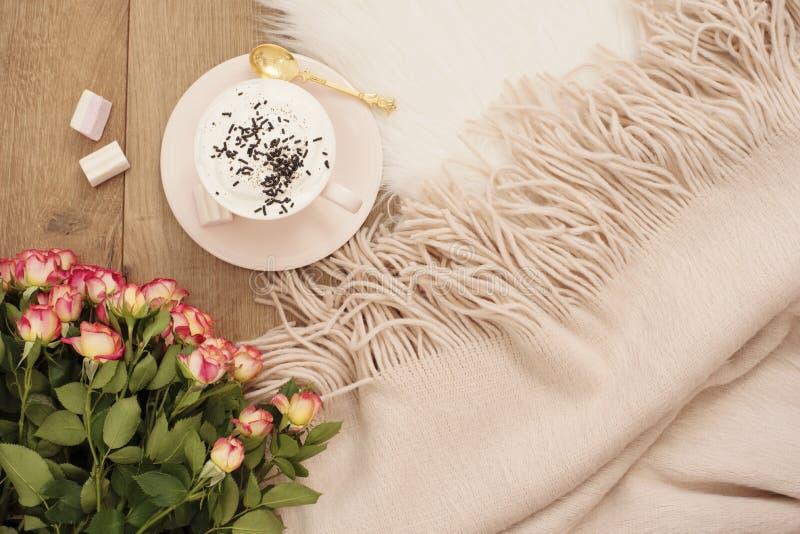 Manhãs acolhedores do inverno Cappuccino, ramalhete das rosas e um lenço morno em um tapete branco da pele no assoalho fotos de stock