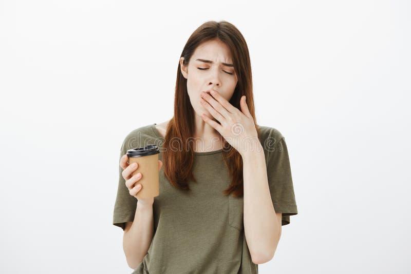 Manhãs do ódio Tiro interno de fêmea europeu atrativo cansado, guardando a xícara de café, bocejando e cobrindo a boca fotografia de stock
