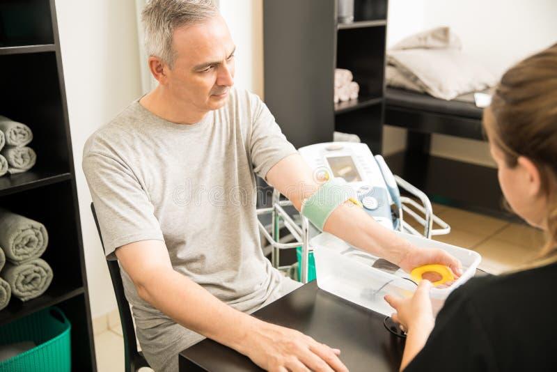 ManhäleriElectrotherapy från terapeut royaltyfria bilder