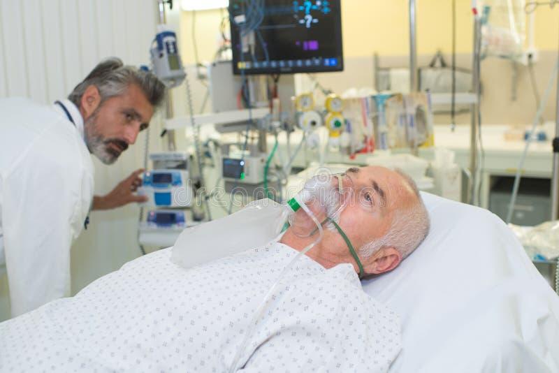Manhälerisyre i sjukhussäng arkivfoto