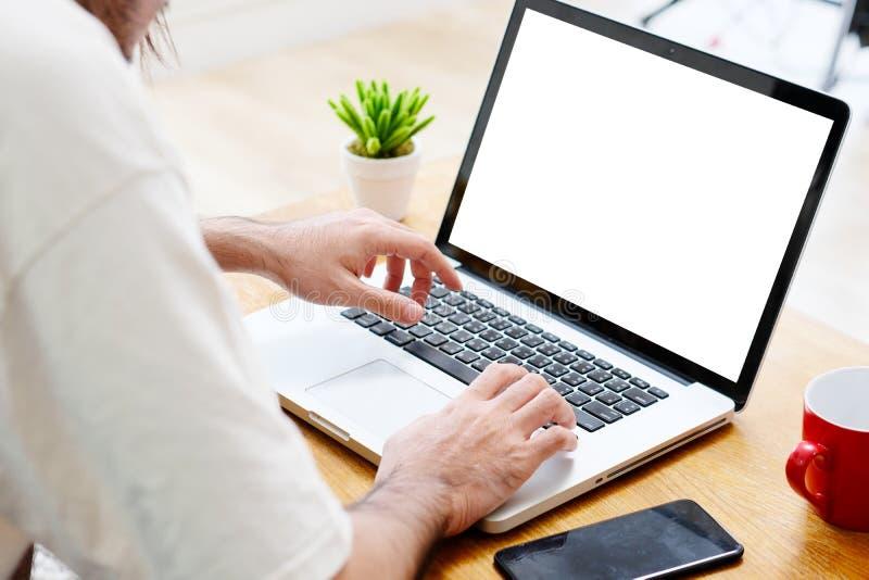 Manhänder genom att använda bärbar datordatoren med den tomma skärmen för åtlöje upp mallbakgrund, affärsteknologi och livsstilba arkivbild