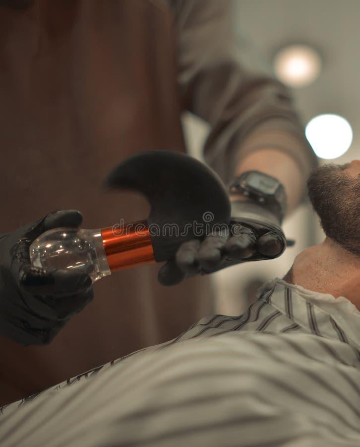 Manhänder i handskar som gör en frisyr för man med mörkt hår och skägg på barberaren, shoppar, stänger sig upp ståenden, kopierin arkivbild