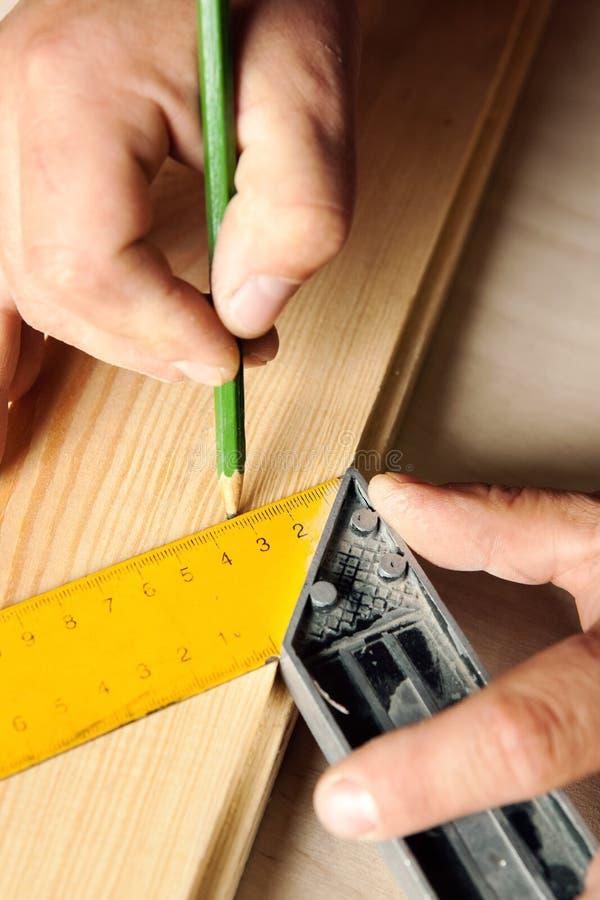 Manhänder med linjal- och blyertspennacloseupen royaltyfri bild