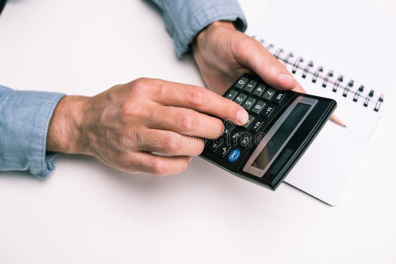 Manhänder med räknemaskinen och notepaden på den vita tabletopen arkivbild