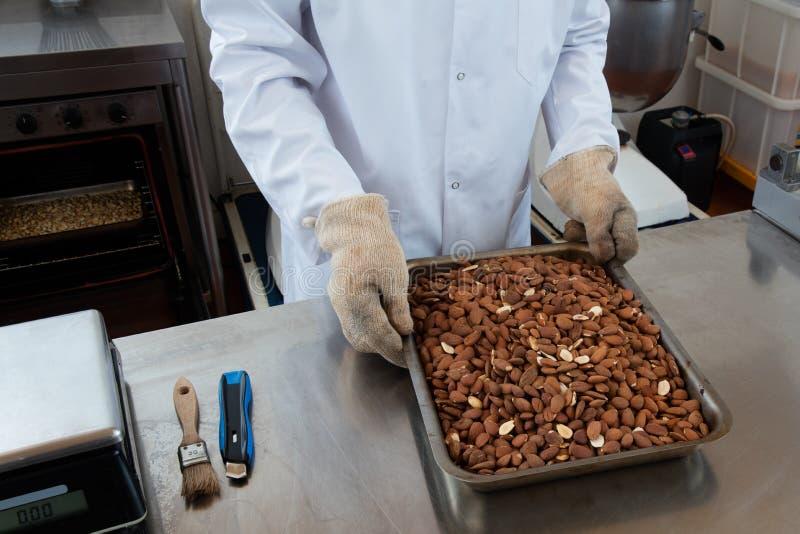 Manhänder med skyddshandskar som tar bort grillade mandlar från ugnen arkivfoto