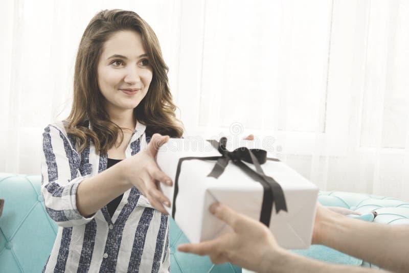 Manhänder som ger för överraskninggåva för ung kvinna asken royaltyfria bilder