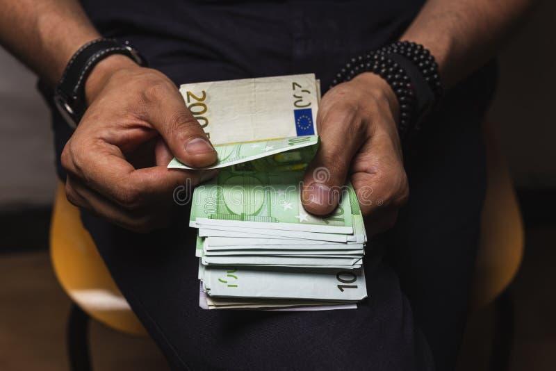 manhänder som räknar stort belopp av sedlar för eurovalutakassa royaltyfri foto