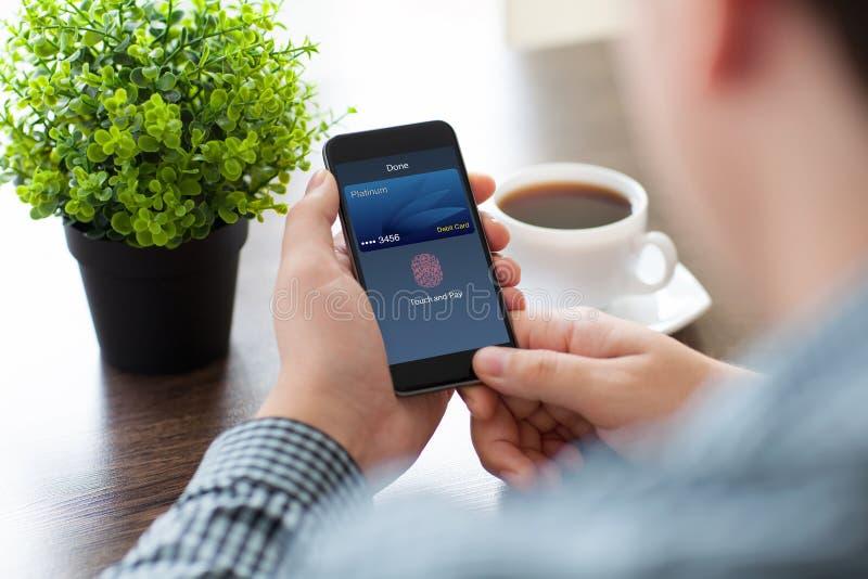 Manhänder som rymmer telefonen med handlag och lön för debiteringkort royaltyfri foto