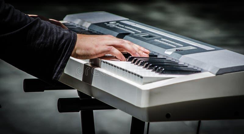 Manhänder som spelar tangentbordpianot, är ett elektroniskt musikinstrument royaltyfria bilder