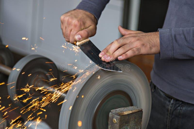 Manhänder som vässar kniven fotografering för bildbyråer