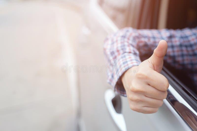 Manhänder som visar tummar upp utmärkthet inom bil-, beundran- och glädjelyckönskanhandelsresande på vägen, medan köra i tra arkivbild
