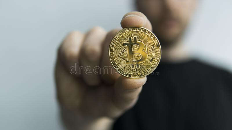 Manhåll i fysisk guld- bitcoin för händer Cryptocurrency Vinst från att bryta crypto valutor Gruvarbetare med mynt royaltyfria bilder