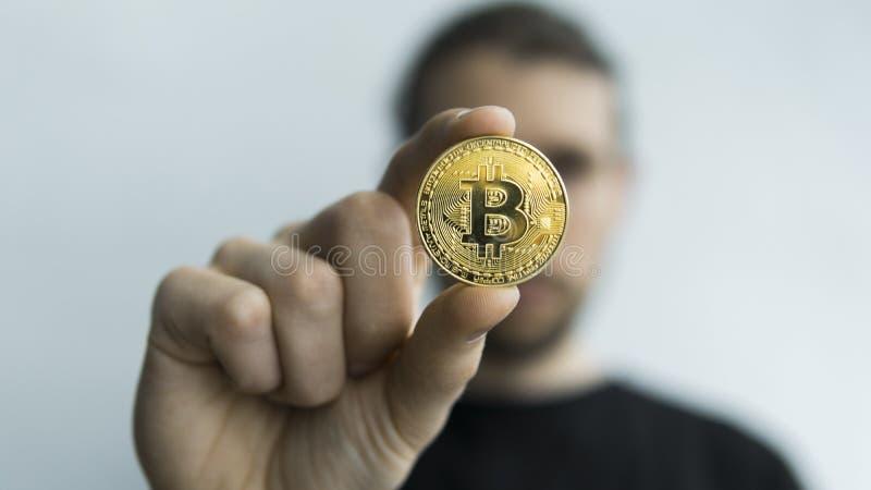 Manhåll i fysisk guld- bitcoin för händer Cryptocurrency Vinst från att bryta crypto valutor Gruvarbetare med mynt arkivbild