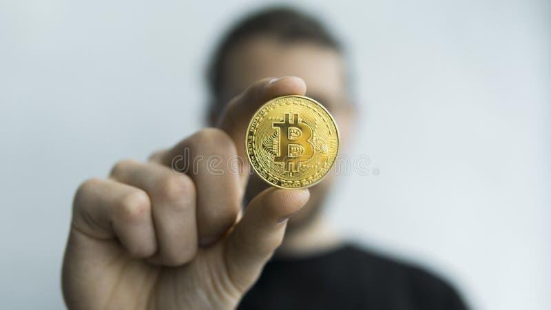 Manhåll i fysisk guld- bitcoin för händer Cryptocurrency Vinst från att bryta crypto valutor Gruvarbetare med mynt royaltyfri fotografi