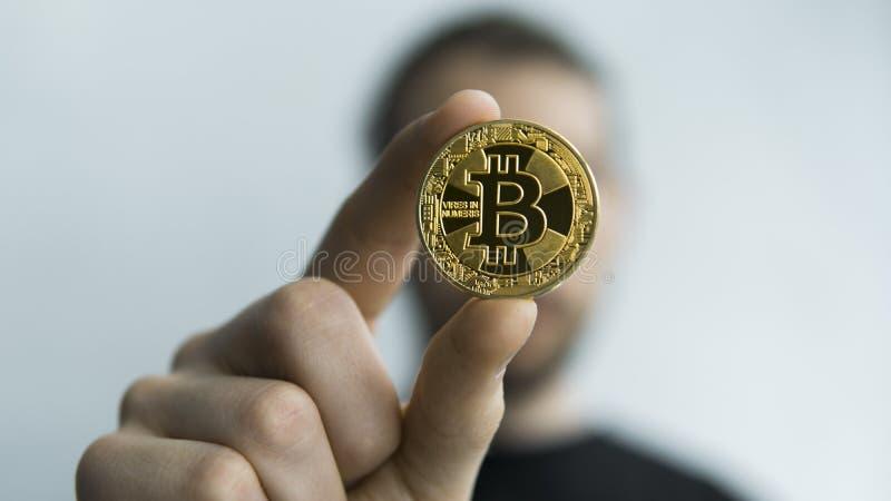 Manhåll i fysisk guld- bitcoin för händer Cryptocurrency Vinst från att bryta crypto valutor Gruvarbetare med mynt royaltyfria foton