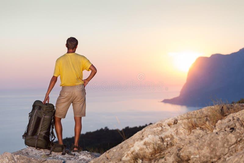 Manhållryggsäck och se soluppgång royaltyfria bilder