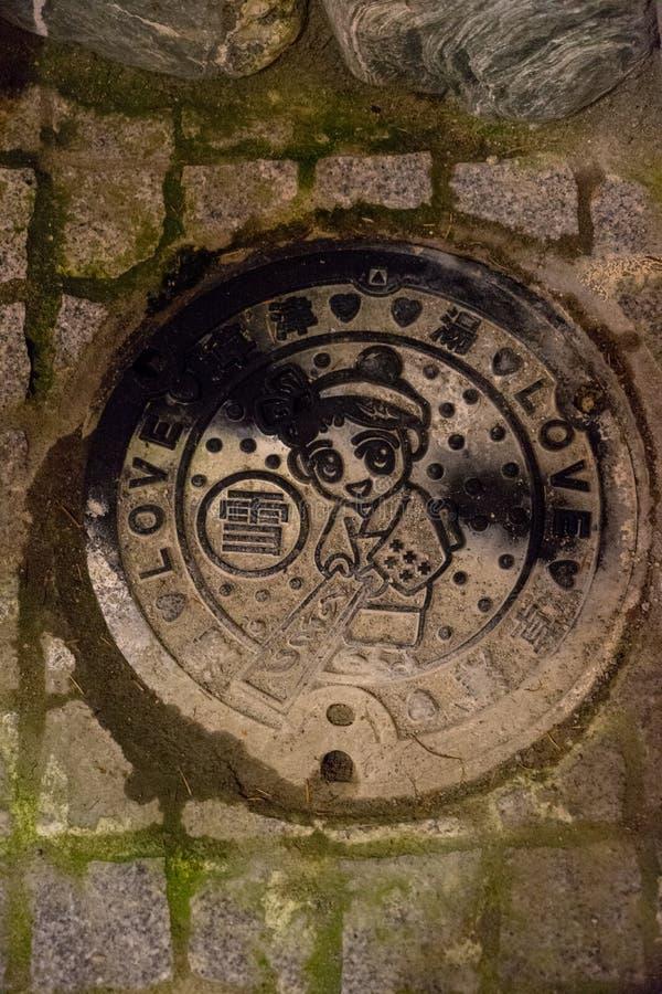Manhålräkning i den Kusatsu staden med designkonst som inristas på den fotografering för bildbyråer
