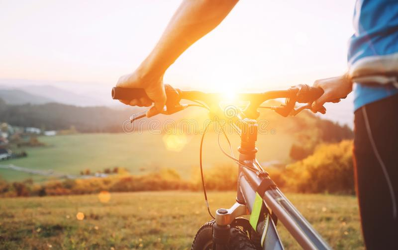 Manh?nder p? slutet f?r cykelstyrninghjul upp bild Man med cykelstaget p? ?verkanten av kullen och att tycka om solnedg?ngen royaltyfri foto