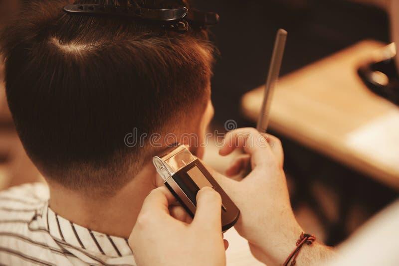 Manhairstylingen och haircutting med hårclipperen i barberare shoppar royaltyfri bild