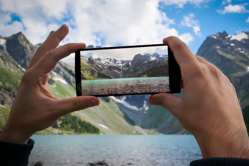 manhand genom att använda mobiltelefonfotoet royaltyfri foto