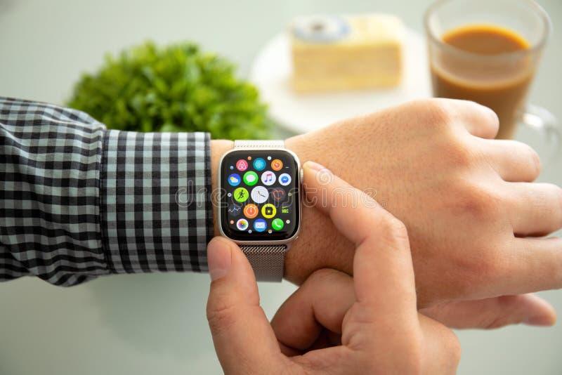 Manhand med Apple klockaserie 4 i hemmet royaltyfri fotografi