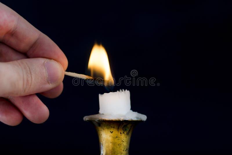 Manhand med Matchstickljusflamman på stearinljuset i ljusstake royaltyfri foto