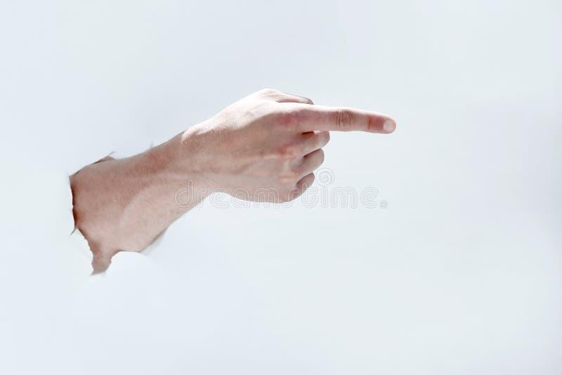 Manhand som bryter till och med papperet och pekar till en kopia av th fotografering för bildbyråer