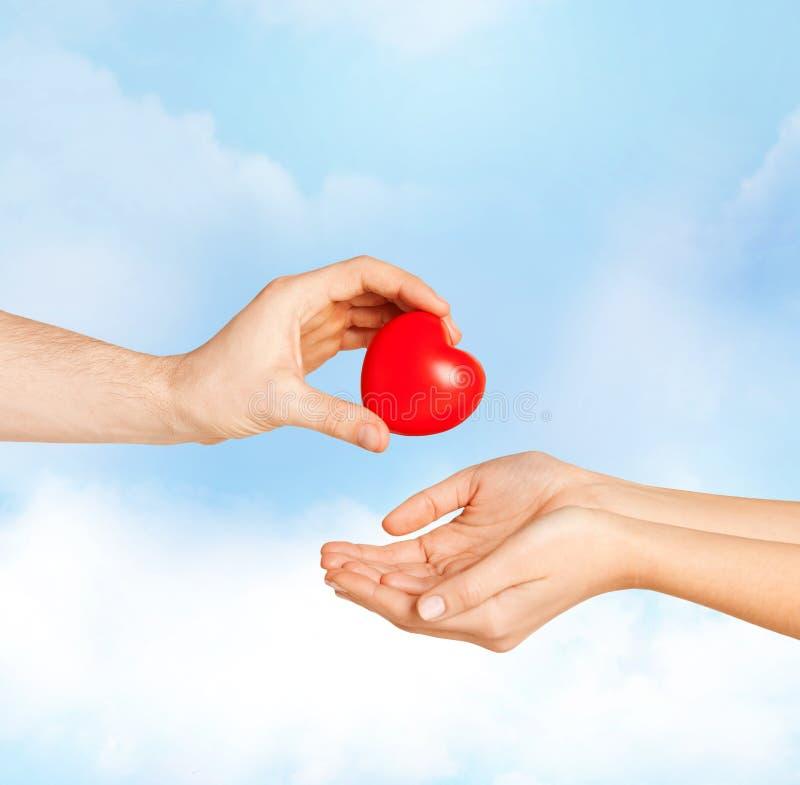 Manhand som ger röd hjärta till kvinnan arkivfoto