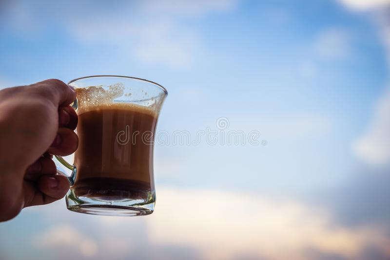 Manhand som lyfter exponeringsglas med morgonkaffe Starta ett begrepp för bra dag Med molnig himmel i bakgrunden fotografering för bildbyråer